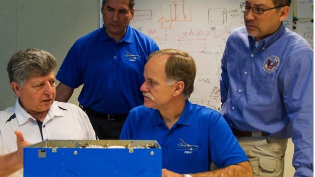 Techniker von Boeing und der US-Verkehrssicherheitsbehörde NTSB vor einem Akku wie er im Dreamliner eingesetzt wird. Das Foto soll die Zusammenarbeit zwischen Boeing und den Behörden symbolisieren.
