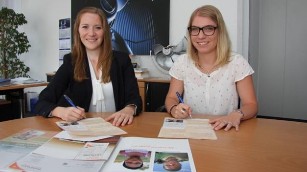 Jennifer Zürn (links) und Marlen Geißler unterzeichnen für die Ziehl-Abegg-Auszubildenden die Patenschaftsübernahme für zwei Kinder in Swasiland.